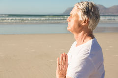 Senior man meditating at beach during sunny day Stock Images