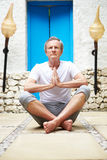 Senior Man Meditating Outdoors At Health Spa Royalty Free Stock Image