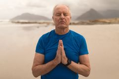 Senior man meditating in prayer position on the beach. Front view of an active senior man meditating in prayer position on the beach royalty free stock photography