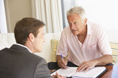 Senior Man Meeting With Financial Advisor At Home Royalty Free Stock Image