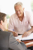 Senior Man Meeting With Financial Advisor At Home Stock Image