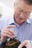 Senior Man Mending Clock Mechanism. Close Up Of Senior Man Mending Clock Mechanism Royalty Free Stock Photos