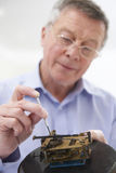 Senior Man Mending Clock Mechanism Royalty Free Stock Photo