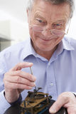 Senior Man Mending Clock Mechanism. Portrait Of Senior Man Mending Clock Mechanism Stock Photography