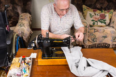 Senior Man Mending Pants with Sewing Machine. High Angle View of Senior Man Mending Pants with Old Fashioned Manual Sewing Machine at Home in Living Room Stock Photos