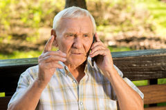 Senior man with mobile phone. Old guy with serious face. Listen to me, son. Giving a wise advice Stock Photo