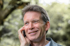 Senior man with mobile phone. Senior man smiling and talking on mobile phone Royalty Free Stock Photos