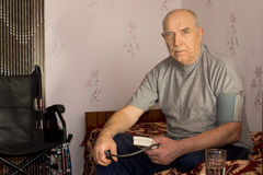 Senior man moniotoring his blood pressure. Using a pressure cuff and sphygmomanometer sitting on his bead at home Stock Photography