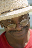 Senior man with moustache, wearing straw hat and spectacles, smiling, close-up, portrait Stock Photo