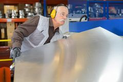 Senior man moving sheet metal. Man Royalty Free Stock Photography