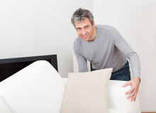 Senior man moving sofa Royalty Free Stock Photo