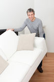 Senior man moving sofa Stock Images