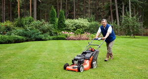 Senior man mowing the lawn. stock photography