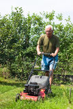 Senior man mowing lawn Royalty Free Stock Photos