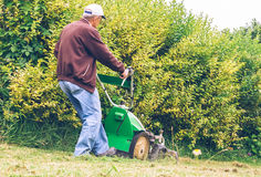 Senior man mowing the lawn with lawnmower Stock Photography