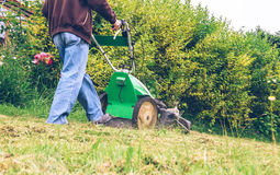 Senior man mowing the lawn with lawnmower Royalty Free Stock Images