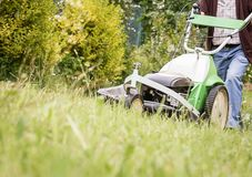 Senior man mowing the lawn with a lawnmower Stock Photography