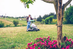 Senior man mowing the lawn with lawnmower royalty free stock photography