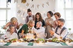 A senior man with multigeneration family celebrating birthday on indoor party. royalty free stock photo