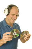 Senior man music head phones. Middle age senior man listening to music cd discs with vintage head phones and holding compact discs Stock Photography