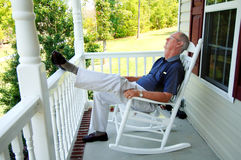 Senior man naps on front porch. A senior man asleep in a rocking chair on the front porch of a house royalty free stock photography