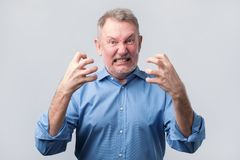 Senior man with nervous crisis. He is in fury. Senior european man in blue shirt with nervous crisis. He is clenching his teeth in fury stock images
