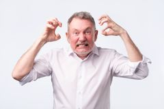 Senior man with nervous crisis. He is in fury. Senior european man in white shirt with nervous crisis. He is clenching his teeth in fury royalty free stock photos