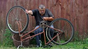Senior man is nervous about very old bicycle to repair stock video footage