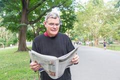 Senior Man in New York. Senior Man Reading Newspaper at Park royalty free stock photography