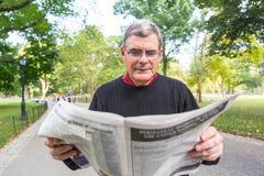 Senior Man in New York. Senior Man Reading Newspaper at Park royalty free stock photos