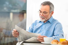 Senior man with a newspaper Stock Photo