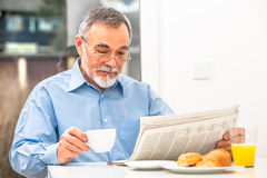 Senior man with a newspaper Stock Photos