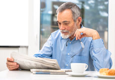 Senior man with newspaper royalty free stock photography