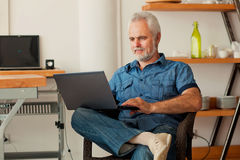 Senior man with notebook sitting at the kitchen Royalty Free Stock Image