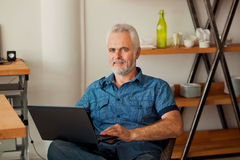 Senior man with notebook sitting at the kitchen Royalty Free Stock Photos