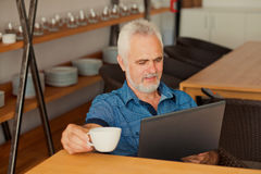 Senior man with notebook sitting at the kitchen an Stock Photography