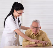 Senior man with nurse. Young pretty nurse holding her hands on the shoulder and hands of old men and smiling. Concept of senior people care Royalty Free Stock Photography