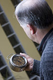 Senior man with old clock. A senior man holding an old alarm clock in his hands, looking at it attentively stock image
