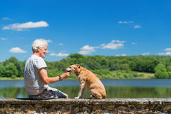 Senior man with old dog in nature landscape Stock Photo