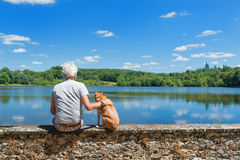Senior man with old dog in nature landscape Stock Photos