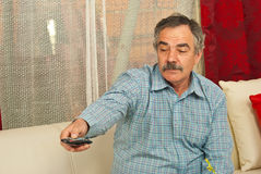 Senior man opening tv with remote control. Senior man sitting on couch in living room and opening tv with remote control Royalty Free Stock Photography