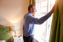 Senior man opens curtains to look at the view from a window Stock Image