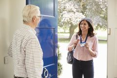 Senior man opens front door to young woman making home visit stock photo