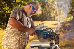 Senior Man Operating a Chop Saw Royalty Free Stock Photo