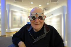 Senior at the optician testing new lenses in a trail frame royalty free stock photography