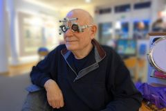 Senior at the optician testing new lenses in a trail frame royalty free stock photo