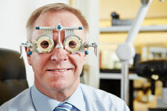 Senior man at optician with trial Royalty Free Stock Image