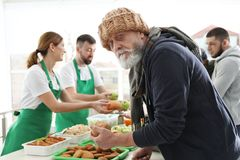 Senior man with other poor people receiving food from volunteers. Senior men with other poor people receiving food from volunteers indoors stock image