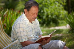 Senior man outdoor. Healthy looking senior man is his late 70s sitting in garden at home and reading book, outdoor Stock Image