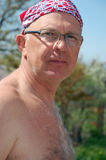 Senior man outdoors. Shirtless senior man wearing glasses and kerchief on his head outdoors stock images